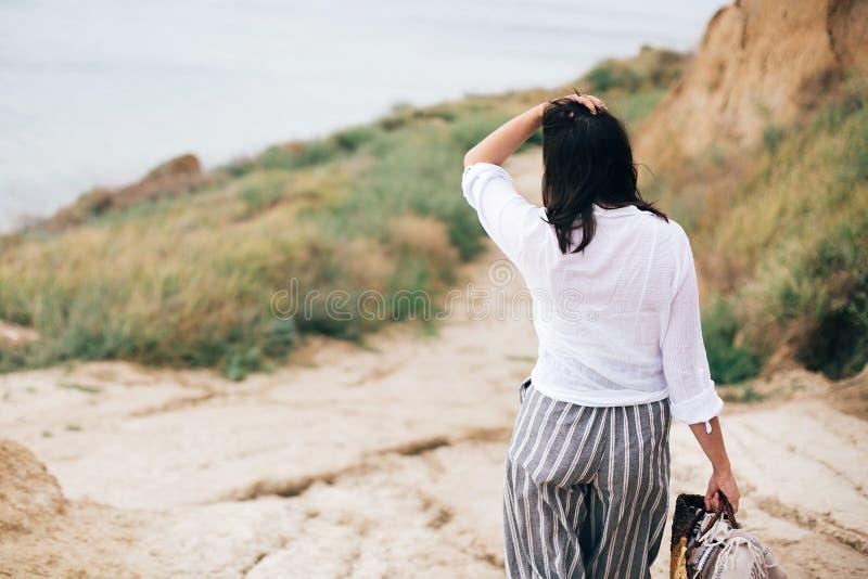 Ragazza alla moda dei pantaloni a vita bassa che si rilassa sulla spiaggia Giovane donna felice di boho in camicia bianca che cam fotografia stock libera da diritti
