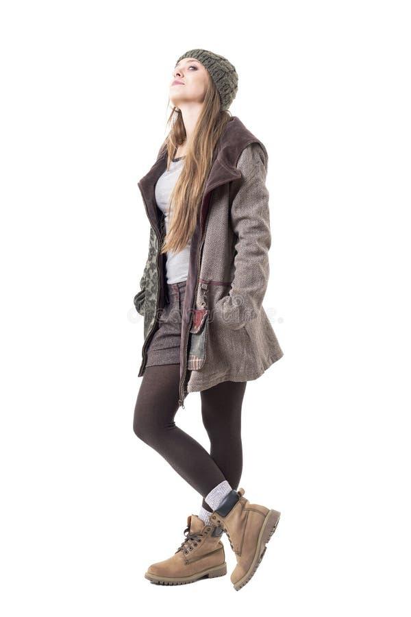 Ragazza alla moda dei pantaloni a vita bassa in vestiti di inverno che portano beanie e cappotto incappucciato che esaminano macc immagine stock