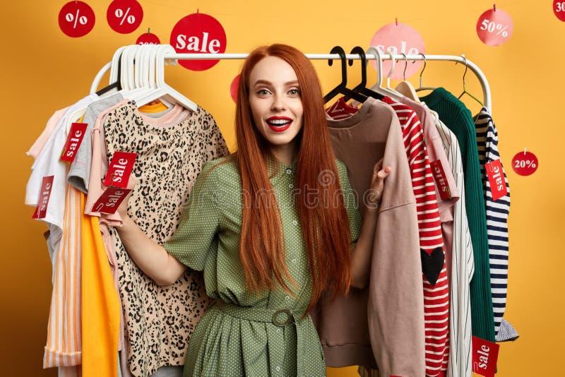 Ragazza alla moda dello zenzero che sceglie i vestiti nel centro commerciale immagine stock