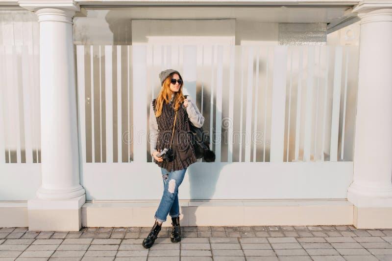 Ragazza alla moda alla moda di joufyl che raffredda sul sole sulla via Giovane donna graziosa in occhiali da sole, inverno caldo  fotografie stock