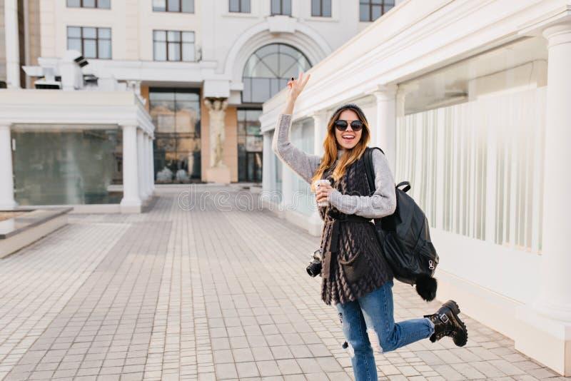 Ragazza alla moda divertente che mostra le vere emozioni positive nel centro urbano Giovane donna con caffè da andare, viaggiando fotografia stock libera da diritti