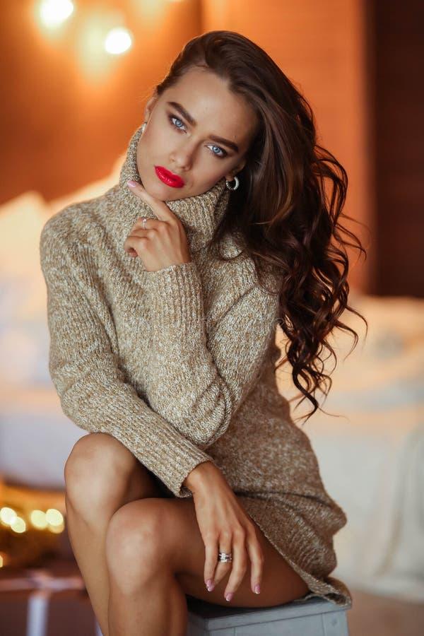 Ragazza alla moda graziosa in vestito con l'acconciatura ed il trucco che si siedono al sof? Ritratto di fascino di modo fotografia stock