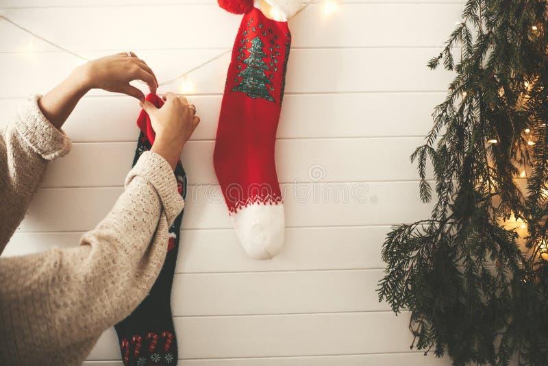 Ragazza alla moda in maglione accogliente che decora stanza per le feste di natale con le calze, la luce della ghirlanda e l'albe fotografia stock