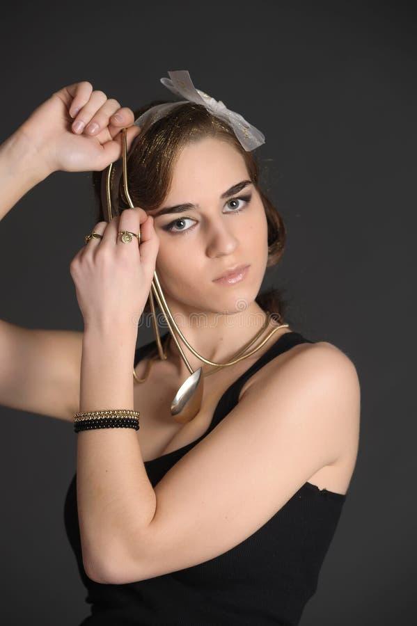 Ragazza alla moda nei gioielli neri dell'oro e del vestito fotografia stock libera da diritti
