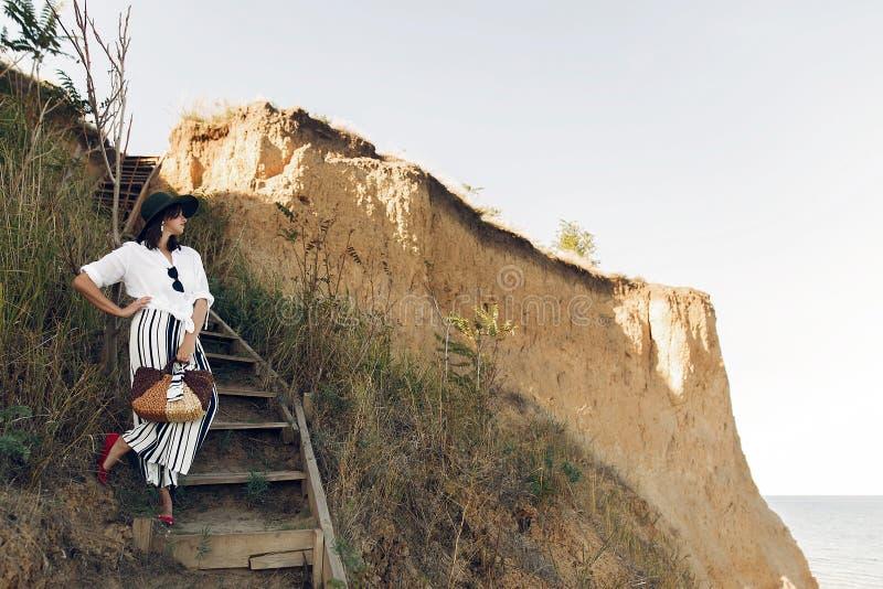 Ragazza alla moda nel sembrare alla moda che si rilassa sulla scogliera della spiaggia sabbiosa in mare alla luce soleggiata Giov fotografia stock libera da diritti