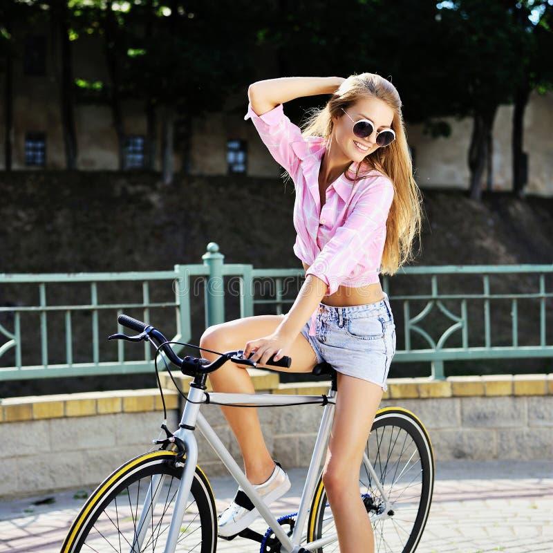 Ragazza alla moda su una bicicletta fissa dell'ingranaggio all'aperto fotografia stock libera da diritti