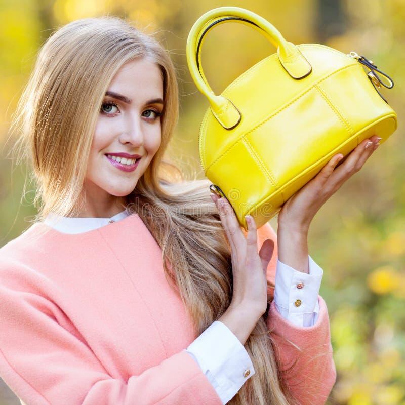 Ragazza alla moda in un cappotto che tiene giallo luminoso della borsa di cuoio in autunno fotografia stock