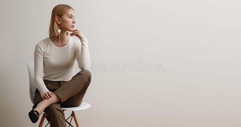 Ragazza alla moda in un maglione bianco e nei pantaloni a quadretti Ritratto di stile di vita della ragazza, emozionale naturali  immagine stock