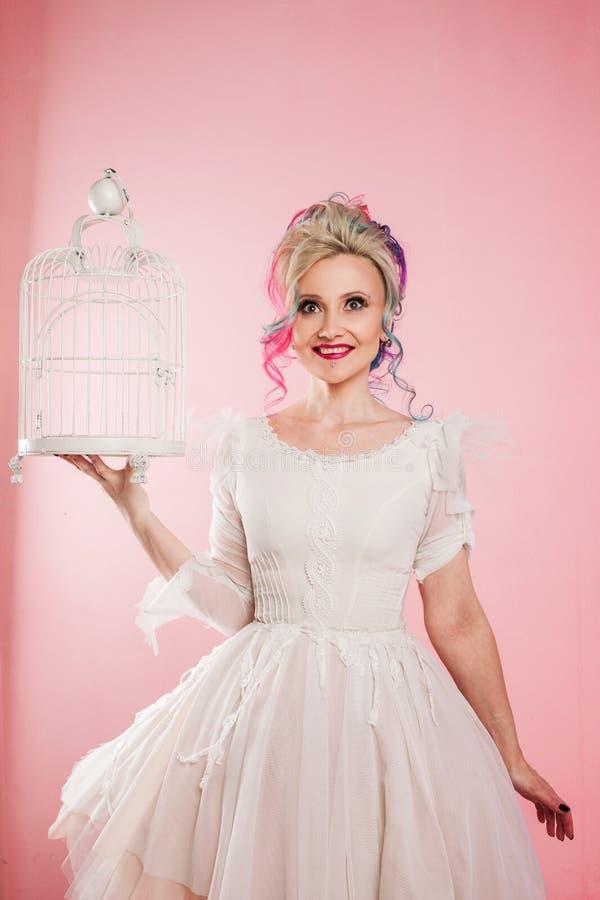 Ragazza alla moda in vestito bianco Coloritura di capelli creativa di acconciatura colorata Multi Concetto con una gabbia per ucc fotografie stock libere da diritti