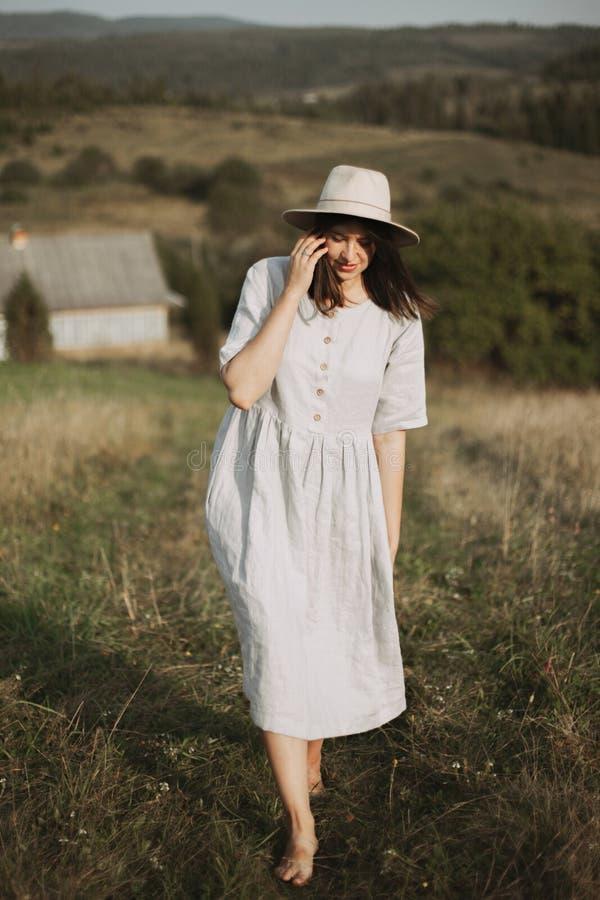 Ragazza alla moda in vestito e cappello di tela che cammina a piedi nudi nell'erba nel campo soleggiato al villaggio Donna di Boh fotografia stock