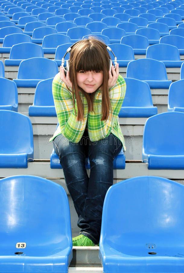 Ragazza alla musica d'ascolto dello stadio immagine stock