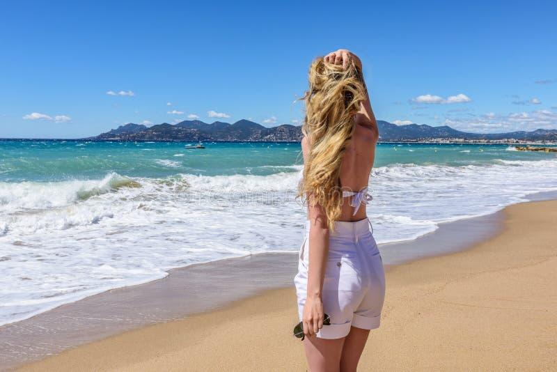 Ragazza alla spiaggia a Cannes, Francia Bello fondo della spiaggia Vista posteriore fotografia stock libera da diritti