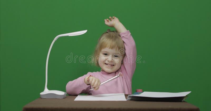 Ragazza alla tabella Solleva la sua mano perch? conosce la risposta alla domanda fotografia stock libera da diritti