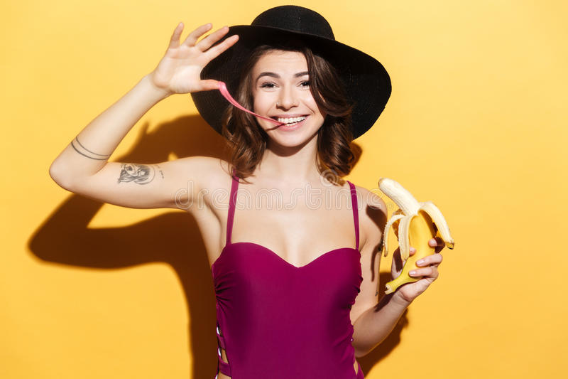 Ragazza allegra in abbigliamento da spiaggia che mastica di gomma da masticare e che tiene banana fotografia stock libera da diritti