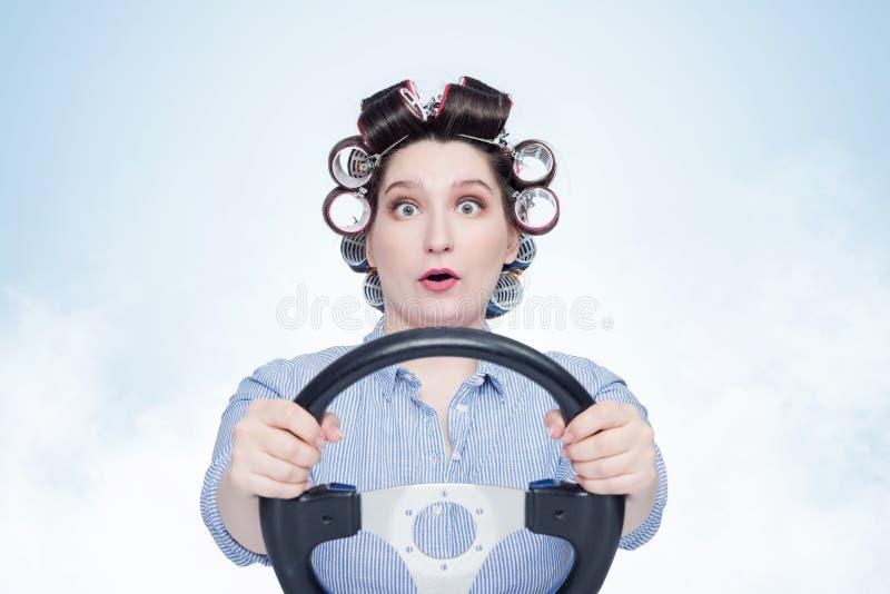 Ragazza allegra in bigodini con il volante Front View Casalinga che conduce un'automobile fotografia stock libera da diritti