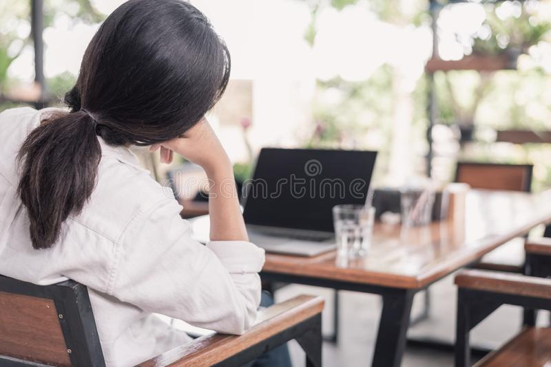 Ragazza allegra che controlla il suo telefono, computer portatile, computer immagine stock