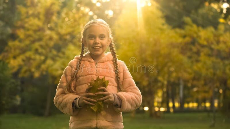 Ragazza allegra con le foglie gialle che esaminano macchina fotografica, umore puerile, parco di autunno fotografie stock libere da diritti