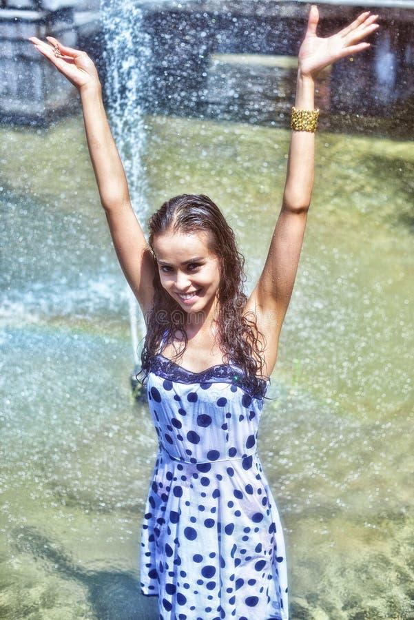 Ragazza allegra con le mani sollevate in un vestito bagnato e nei capelli marroni che posano sui precedenti della fontana immagini stock libere da diritti