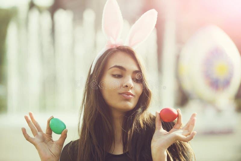 Ragazza allegra con le orecchie ottimistiche del coniglietto che posano con le uova colorate, fotografia stock libera da diritti