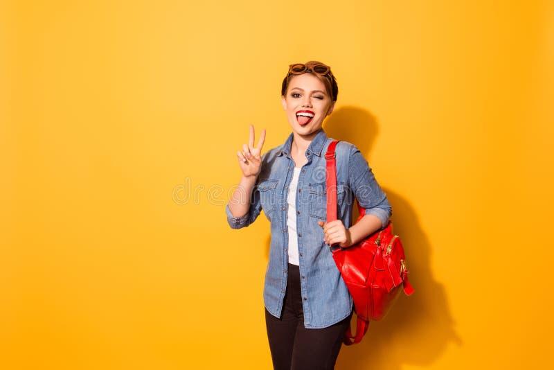 Ragazza allegra con rossetto e la lingua rossi fuori nella s alla moda fotografia stock