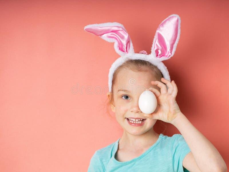 Ragazza allegra del piccolo bambino con le orecchie del coniglietto con l'uovo bianco di pasqua su fondo rosa fotografia stock libera da diritti