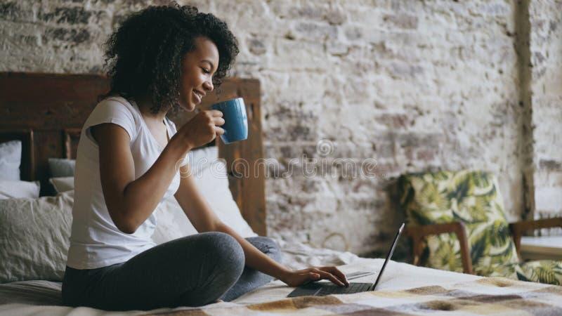 Ragazza allegra della corsa mista che scrive sul computer portatile per la divisione dei media sociali che si siedono a letto a c fotografie stock