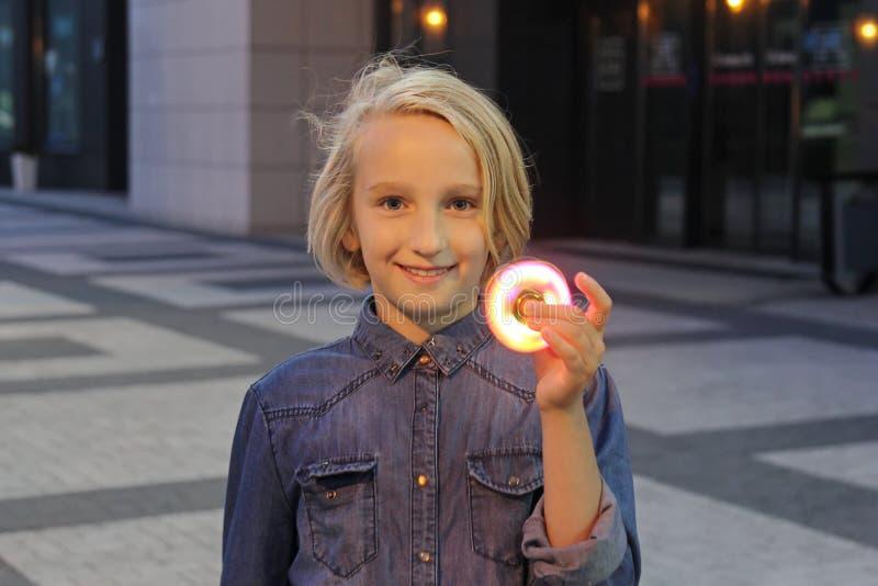 Ragazza allegra della scuola che gioca con un filatore luminoso di irrequietezza, uguagliante all'aperto Un giocattolo d'avanguar fotografia stock