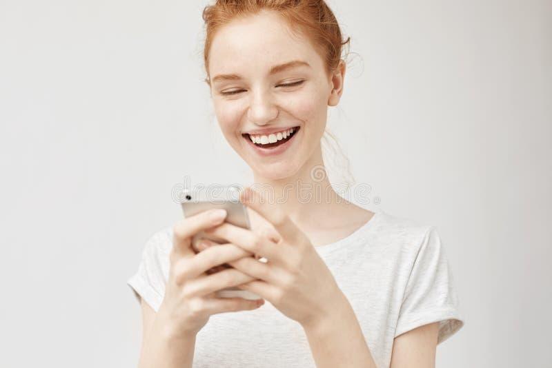 Ragazza allegra della testarossa che sorride esaminando lo schermo del telefono immagini stock libere da diritti