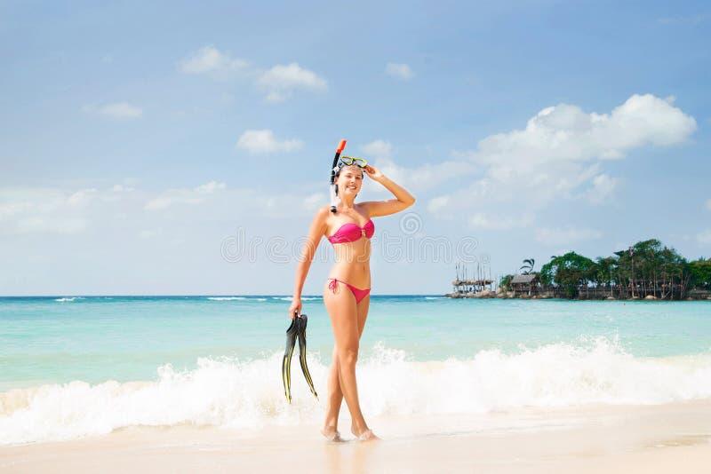 Ragazza allegra e bella con l'ente esile che posa sul litorale con una maschera dello scuba immagini stock libere da diritti