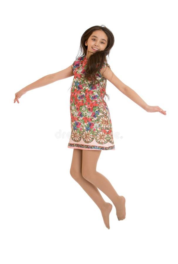 Ragazza allegra nei salti variopinti del vestito fotografia stock