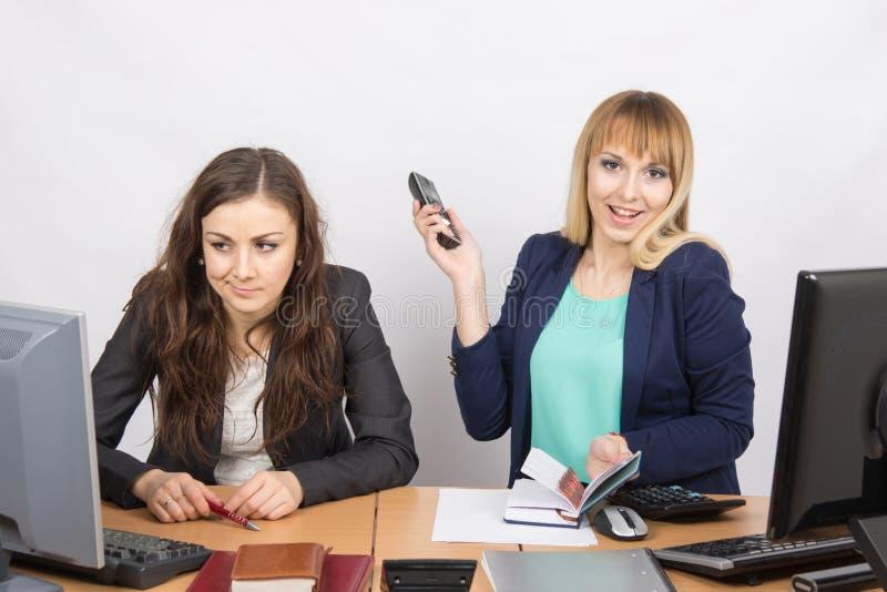 Ragazza allegra nell'ufficio con un telefono in sua mano vicino al collega infelice immagini stock libere da diritti