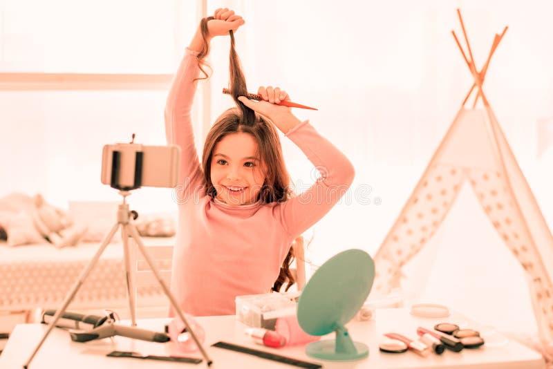 Ragazza allegra positiva che spazzola i suoi capelli sulla macchina fotografica fotografia stock