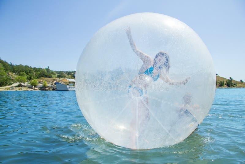 Ragazza allegra in un aerostato che galleggia sull'acqua. fotografia stock