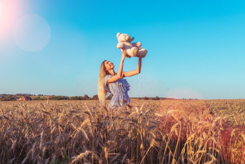 Ragazza allegra in un vestito blu che gioca con il giocattolo dell'orsacchiotto di estate su un giacimento di grano Risate sorrid fotografie stock