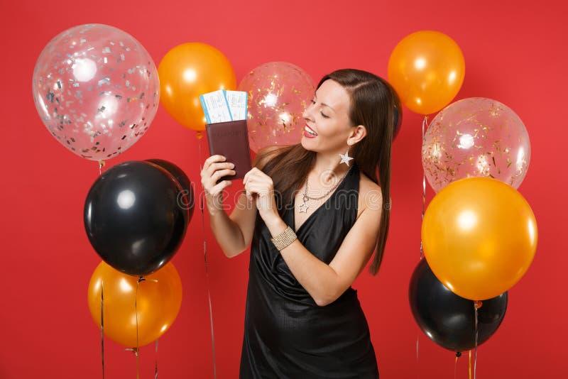 Ragazza allegra in vestito nero che celebra considerando i biglietti del passaggio di imbarco del passaporto in mani sull'aria ro fotografia stock libera da diritti