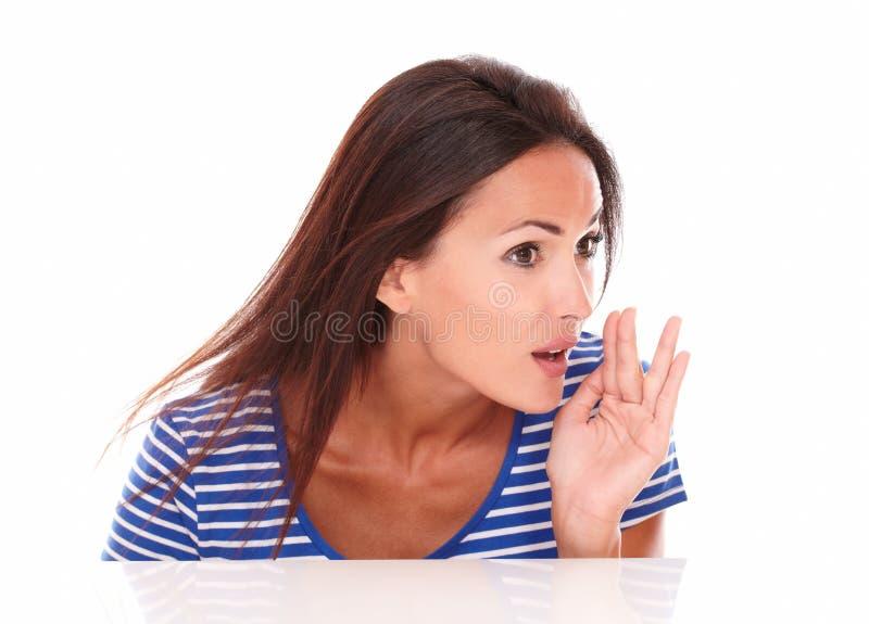 Ragazza amichevole in maglietta blu che bisbiglia un segreto fotografie stock libere da diritti
