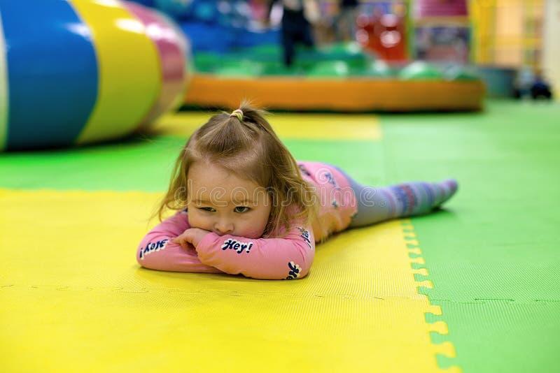 Ragazza annoiata che si trova sulla stuoia di collegamento del pavimento nel playgound dei bambini Il bambino si trova sulle pias immagine stock