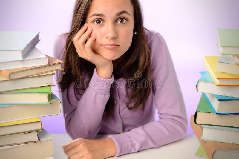 Ragazza annoiata dello studente che si siede fra i libri della pila immagine stock libera da diritti