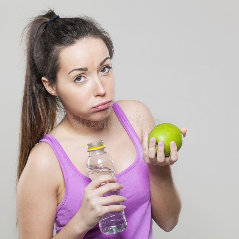 Ragazza annoiata di forma fisica 20s che mette in discussione il gusto dell'una mela verde con acqua immagini stock libere da diritti
