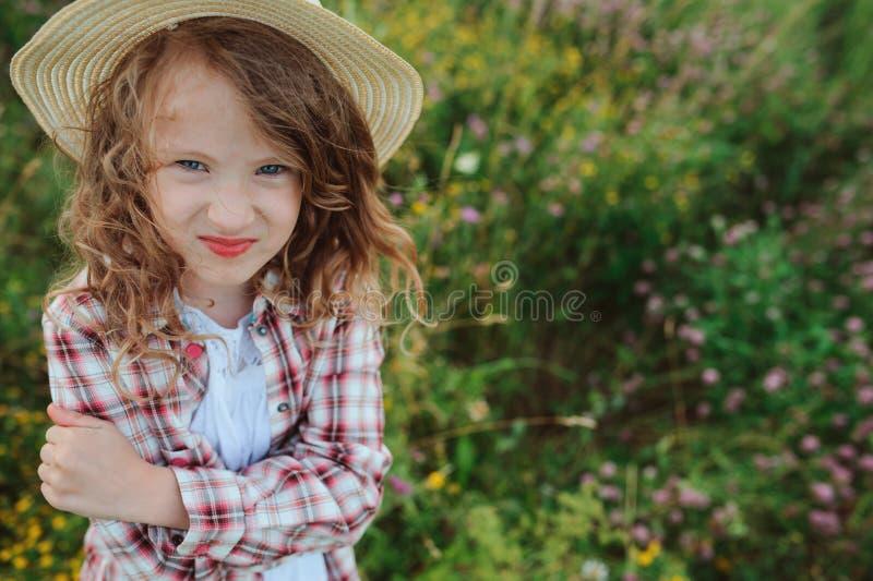 Ragazza arrabbiata del bambino in camicia e cappello di plaid stile country immagine stock