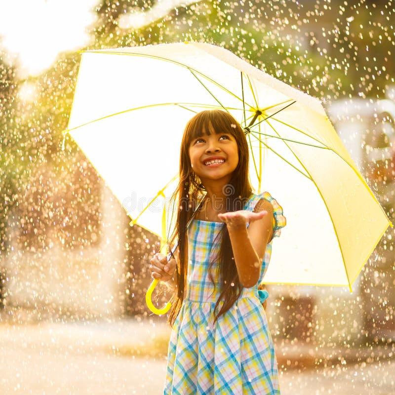 Ragazza asiatica abbastanza giovane nella pioggia fotografia stock