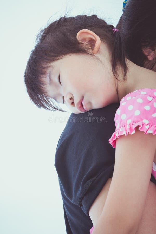 Ragazza asiatica adorabile che dorme sulla spalla della mamma, su backgroun bianco immagine stock