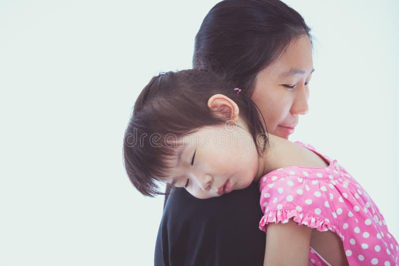 Ragazza asiatica adorabile che dorme sulla spalla della mamma, su backgroun bianco fotografia stock