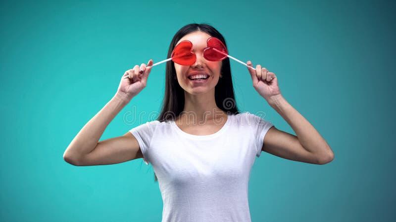 Ragazza asiatica allegra divertendosi tenendo le lecca-lecca dolci in occhi anteriori, buon umore fotografia stock libera da diritti