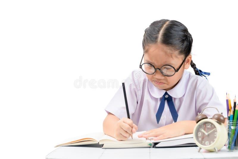 Ragazza asiatica annoiata e stanca dello studente che fa compito fotografia stock