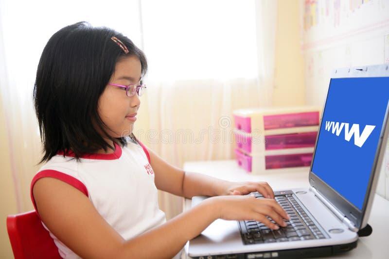 Ragazza asiatica che gioca con il computer portatile sulla tabella fotografia stock libera da diritti