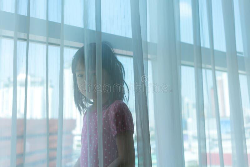Ragazza asiatica che gioca dietro la tenda pura dalla grande finestra con la e immagini stock libere da diritti