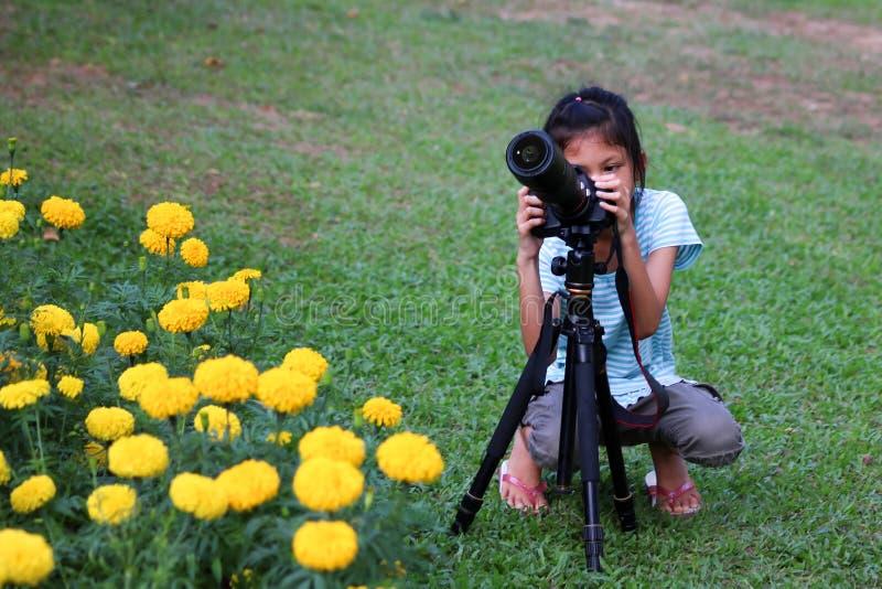 Ragazza asiatica che impara utilizzare la macchina fotografica del dslr nel giardino immagine stock libera da diritti