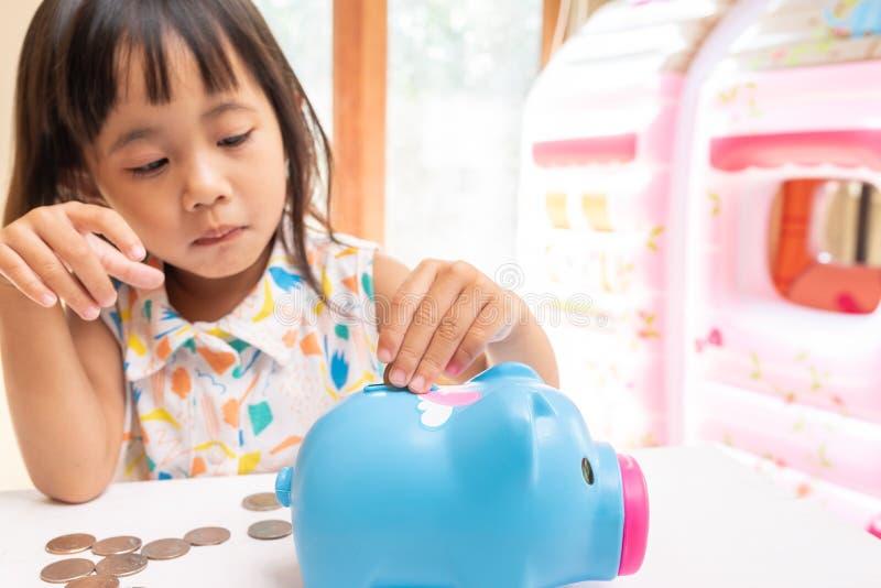 Ragazza asiatica che mette moneta nel porcellino salvadanaio per soldi di risparmio Fuoco selettivo della mano del bambino fotografia stock