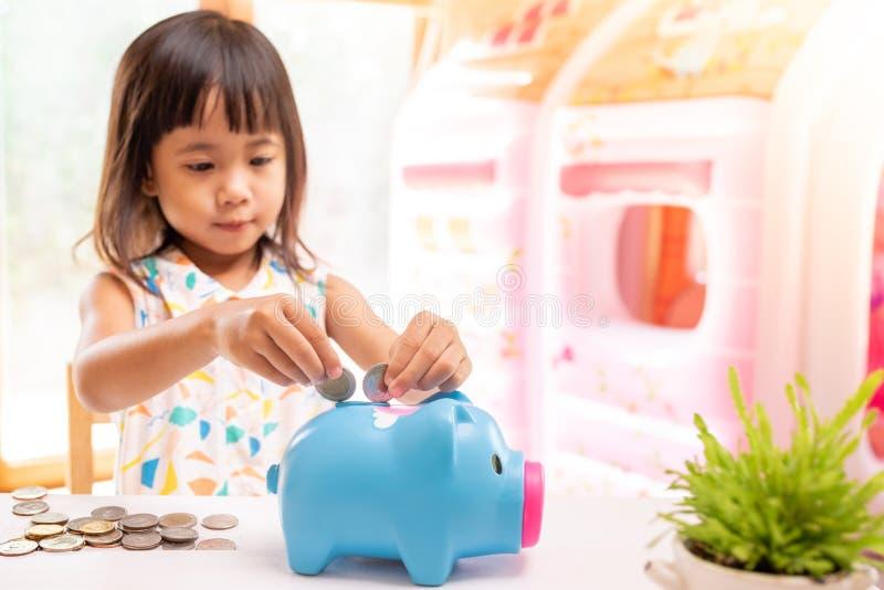 Ragazza asiatica che mette moneta nel porcellino salvadanaio per soldi di risparmio Fuoco selettivo della mano del bambino immagine stock
